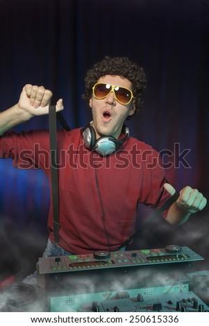 Portrait of cheerful and dancing disc jockey. - stock photo