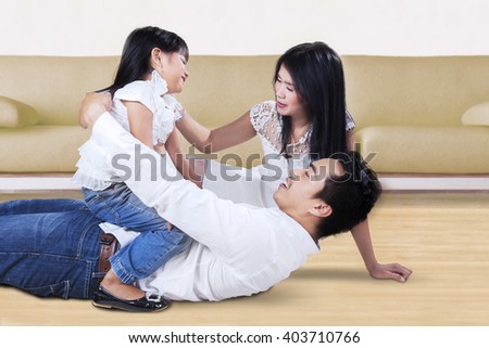 Portrait of cheerful Asian family having fun and laughing together on the floor at home - stock photo