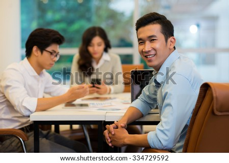Portrait of cheerful Asian startup company founder having meeting with his colleagues - stock photo
