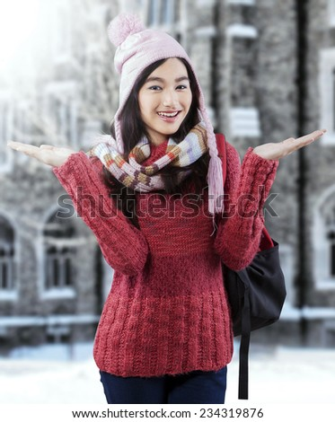 Portrait of cheerful asian student wearing a knitted sweater, standing outdoors - stock photo