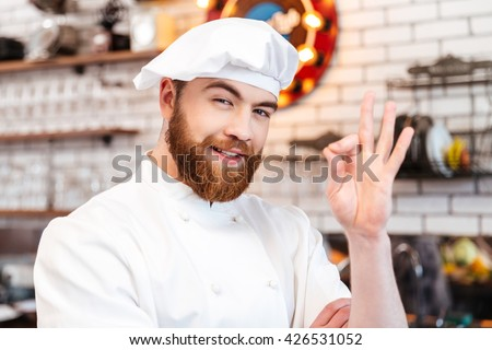 Portrait of cheerful attractive chef cook showing ok sign on the kitchen - stock photo