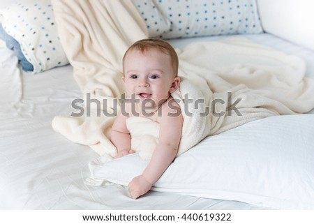 Portrait of cheerful baby boy lying on big pillow under white blanket - stock photo