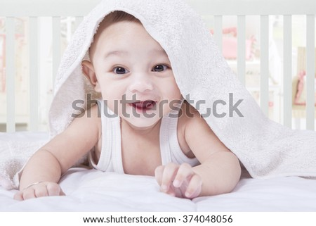Portrait of cheerful baby boy try to crawl under white towel on the bedroom, shot at home