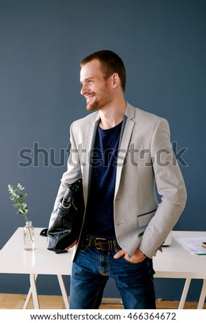 Portrait of cheerful bearded man with handbag against of table and grey wall looking away