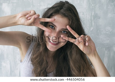 Portrait of cheerful beautiful brunette with two peace signs against of cement wall