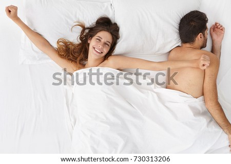 Portrait of cheerful beautiful woman wearing no clothes, lying in bed under white cover and stretching her arms to sidewards, having happy broad smile on her pretty face, rejoicing at new amazing day
