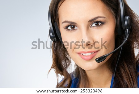 Portrait of cheerful beautiful young support phone operator in headset, with copyspace area - stock photo