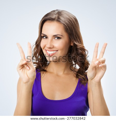 Portrait of cheerful beautiful young woman in smart casual violet clothing, showing two fingers or victory gesture, against grey background - stock photo