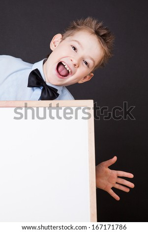 Portrait of cheerful boy pointing on white banner on the black background