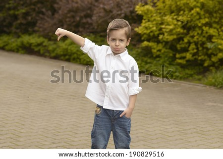 Portrait of cheerful boy showing thumbs down gesture - stock photo