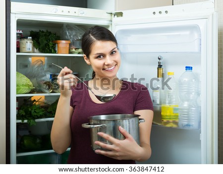 Portrait of cheerful brunette dusting in residential kitchen - stock photo