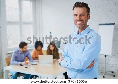 Portrait of cheerful business man standing in modern creative office with employees in background