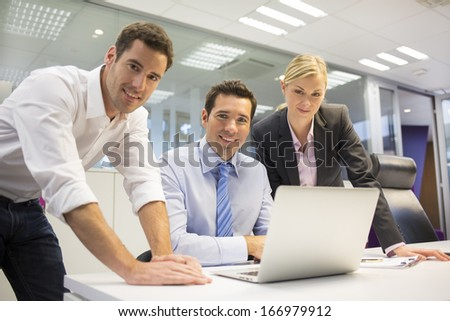 Portrait of cheerful business team in office, looking camera  - stock photo