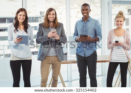 Portrait of cheerful business team using technology while standing at office - stock photo