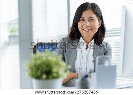 Portrait of cheerful business woman looking at the camera - stock photo
