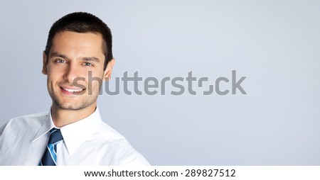 Portrait of cheerful businessman, against grey background. Copyspace blank area for slogan or text. Caucasian male model at studio shot. Business and success concept. - stock photo