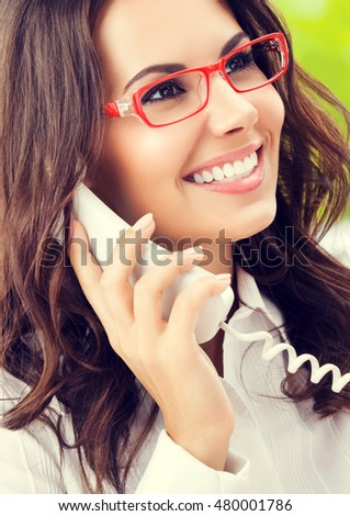 Portrait of cheerful businesswoman or support phone worker on phone