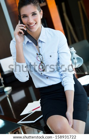Portrait of Cheerful businesswoman talking on phone standing in her office