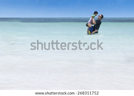 Portrait of cheerful children enjoy holiday on beach with their father - stock photo
