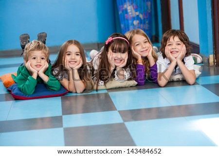 Portrait of cheerful children lying in a row on floor at preschool - stock photo