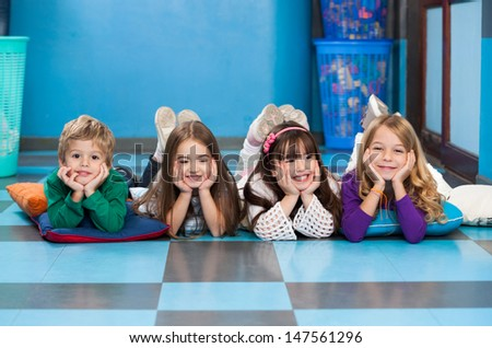 Portrait of cheerful children lying in a row on floor in classroom - stock photo