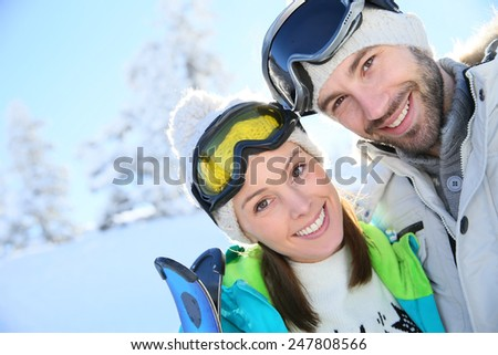 Portrait of cheerful couple in snowy mountain - stock photo