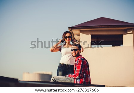 Portrait of cheerful couple sitting on the roof against the sky - stock photo