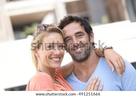 Portrait of cheerful couple standing outside
