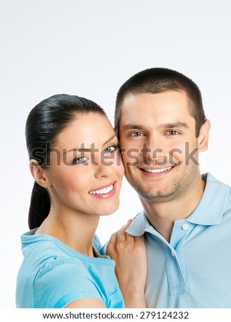 Portrait of cheerful couple, with copyspace blank area for text or slogan, on grey background - stock photo