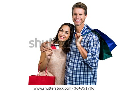 Portrait of cheerful couple with shopping bags and credit card against white background - stock photo