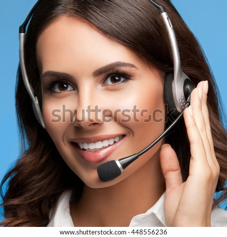 Portrait of cheerful customer support female phone operator in headset, over blue background - stock photo