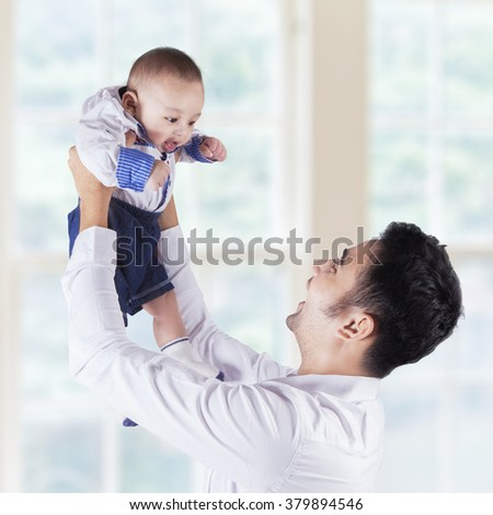 Portrait of cheerful dad lift up his male infant near the window at home - stock photo