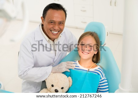 Portrait of cheerful dentist and his young patient - stock photo