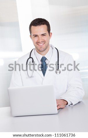 Portrait of cheerful doctor sitting at the desk working on laptop - stock photo