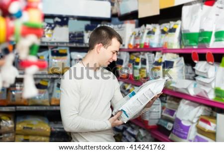 Portrait of cheerful european guy selecting vet food in petshop - stock photo