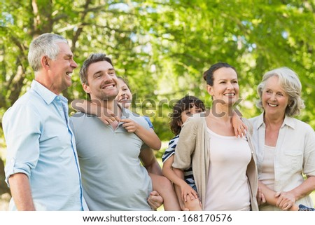 Portrait of cheerful extended family playing in the park - stock photo