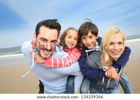 Portrait of cheerful family at the beach - stock photo