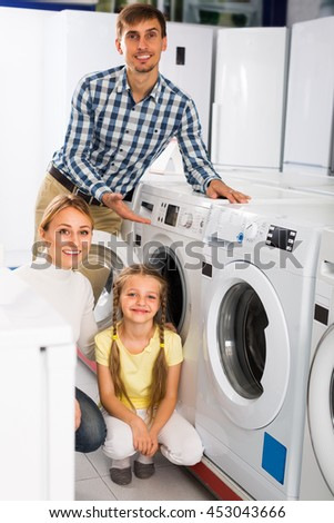 portrait of cheerful family choosing laundry washer in appliance shop - stock photo