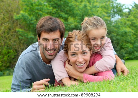 Portrait of cheerful family laying on grass - stock photo