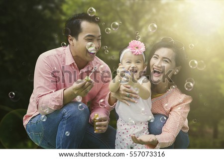 Portrait of cheerful family playing with soap bubbles while laughing together in the park