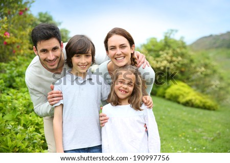 Portrait of cheerful family standing in home garden - stock photo