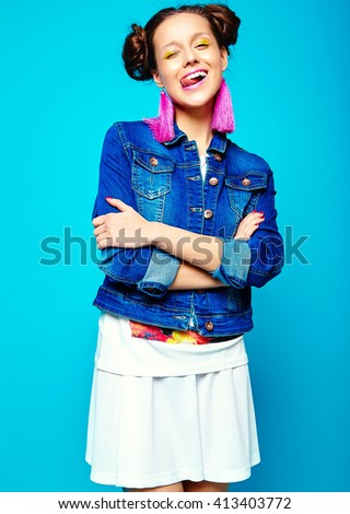 portrait of cheerful fashion hipster girl in casual hipster  summer clothes jeans jacket on blue background  - stock photo