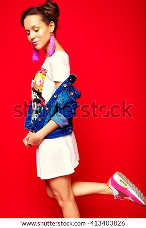 portrait of cheerful fashion hipster girl in casual hipster  summer clothes jeans jacket on red background  - stock photo