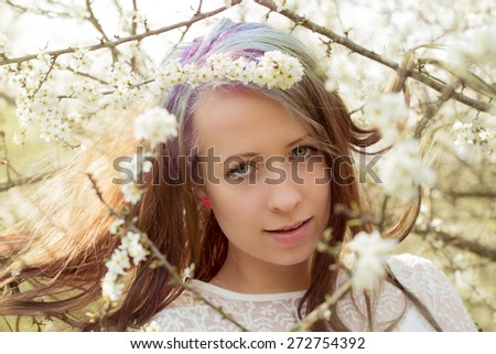 Portrait of cheerful fashionable woman in spring blooming tree, with flowers in hair, retro vintage color - stock photo