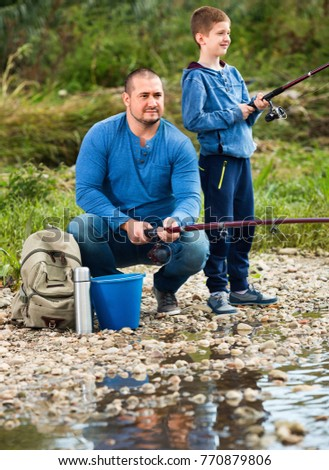 Portrait of  cheerful father and cute son fishing with rods in summer day