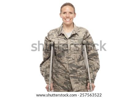 Portrait of cheerful female airman on crutches - stock photo