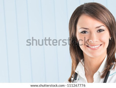 Portrait of cheerful female doctor at office, with copyspace - stock photo