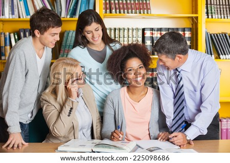 Portrait of cheerful female student with teachers and classmates in university library - stock photo