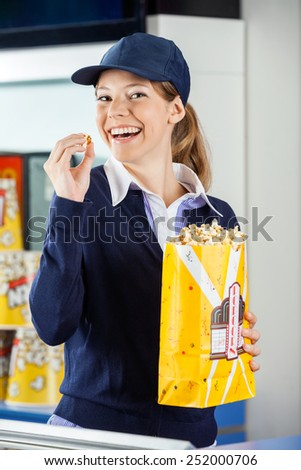 Portrait of cheerful female worker eating popcorn from paperbag at cinema concession stand - stock photo