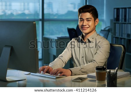 Portrait of cheerful Filipino businessman  at his workplace - stock photo